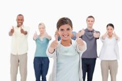 Close-up van een glimlachende vrouw die duim-omhooggaand met mensen geven beh Stock Foto