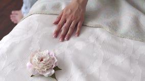 Close-up van een hand die van een jong meisje op het bed, naast een pioenbloem liggen stock footage