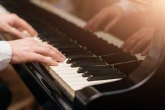 Close-up van een hand die van de muziekuitvoerder ` s de piano spelen stock foto