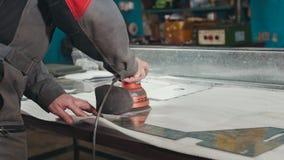 Close-up van een handdieschuurmachine door een arbeider bij de fabriek en het schuren van een metaaldeel wordt gecontroleerd stock afbeeldingen