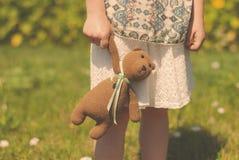 Close-up van een handtas met een boeket en een gebreide beer die uit het in de handen van een meisje op een weide gluren met stock foto