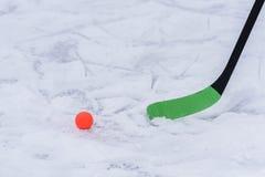 Close-up van een hockeystok met een oranje bal Royalty-vrije Stock Afbeelding