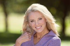 Close-up van een Hogere Vrouw die bij de Camera bij het Park glimlachen stock afbeeldingen