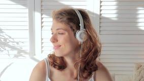 Close-up van een jonge aantrekkelijke vrouw die met hoofdtelefoons aan muziek luisteren stock video