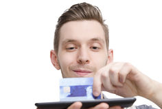 Close-up van een jonge creditcard van de kerelholding op een tablet stock foto's