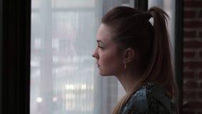 Close-up van een jonge droevige vrouw die uit het venster kijken stock video