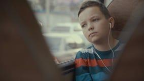 Close-up van een jonge jongen die door bus wordt geschoten door stad reizen die Hij luistert aan muziek stock video