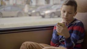 Close-up van een jonge jongen die door bus wordt geschoten door stad reizen die Hij die sociaal netwerk op zijn smartphone gebrui stock video