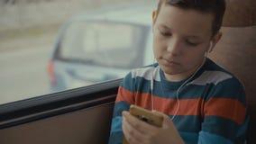 Close-up van een jonge jongen die door bus wordt geschoten door stad reizen die Hij die sociaal netwerk op zijn smartphone gebrui stock videobeelden