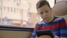 Close-up van een jonge jongen die door bus wordt geschoten door stad reizen, die sociaal netwerk op zijn computertablet die gebru stock footage