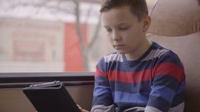 Close-up van een jonge jongen die door bus wordt geschoten door stad reizen, die sociaal netwerk op zijn computertablet die gebru stock video