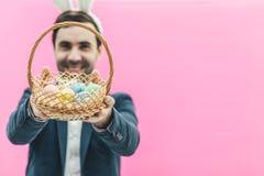 Close-up van een jonge knappe mens die zich op een roze achtergrond bevinden Op het hoofd zijn konijntjesoren Tegelijkertijd houd stock afbeelding