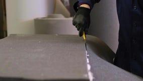 Close-up van een jonge mens in een meubilairfabriek die de bovenmatige schuimdelen van de bank snijdt stock videobeelden
