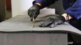 Close-up van een jonge mens in een meubilairfabriek die de bovenmatige schuimdelen van de bank snijdt stock video