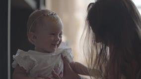 Close-up van een jonge vrouw die met haar mooi glimlachend babymeisje thuis spelen Concept een gelukkige familie, één kind stock video