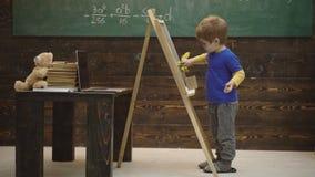 Close-up van een jongen dat met krijt op een raad schrijft Kleine kunstenaarsverven op een houten achtergrond Concept fijn art. stock videobeelden