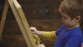 Close-up van een jongen dat met krijt op een raad schrijft Mooie peuterjongen die op bord op houten achtergrond trekken stock footage