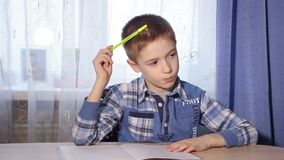 Close-up van een jongen die thuiswerk binnen doen bij een lijst stock videobeelden
