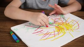 Close-up van een klein kind die heldere kleurenkleurpotloden of potloden trekken op papier terwijl het zitten bij een houten lijs stock videobeelden