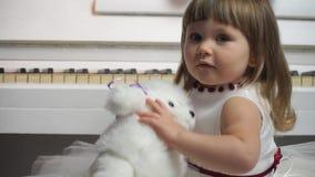 Close-up van een klein meisje met een stuk speelgoed hond op een achtergrond van piano stock videobeelden