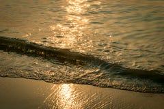 Close-up van een kleine die golf op de kust door de zon wordt aangestoken stock afbeeldingen