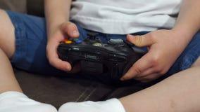 Close-up van een kleine jongen die een bedieningshendel thuis houden en videospelletjes spelen stock video