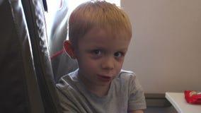 Close-up van een kleine jongen die uit het venster van het vliegtuig kijken stock footage
