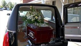 Close-up van een kleurrijke kist in een lijkwagen of een kapel vóór begrafenis of begrafenis bij begraafplaats wordt geschoten di stock videobeelden