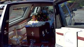 Close-up van een kleurrijke kist in een lijkwagen of een kapel vóór begrafenis of begrafenis bij begraafplaats wordt geschoten di stock footage