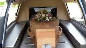 Close-up van een kleurrijke kist in een lijkwagen of een kapel vóór begrafenis of begrafenis bij begraafplaats wordt geschoten di stock video