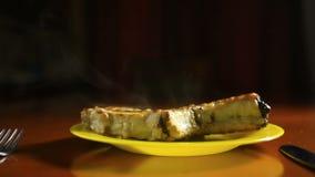 Close-up van een kotelet op een been op een grill wordt gekookt die Het geroosterde vlees ligt op een schotel met geroosterde gro stock video