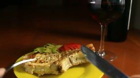 Close-up van een kotelet op een been op een grill wordt gekookt die Het geroosterde vlees ligt op een schotel met geroosterde gro stock videobeelden