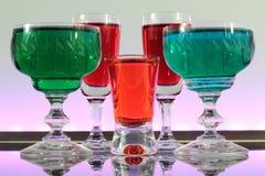 Close-up van een lijn van kleurrijke cocktails die op de bar met geleide verlichting rusten bij een club Stock Afbeelding