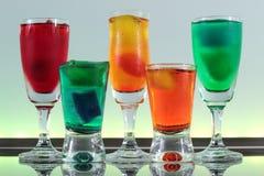 Close-up van een lijn van kleurrijke cocktails die op de bar met geleide verlichting rusten bij een club Royalty-vrije Stock Afbeeldingen