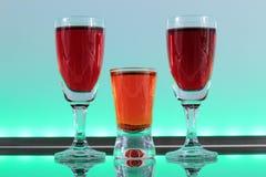 Close-up van een lijn van kleurrijke cocktails die op de bar met geleide verlichting rusten bij een club Stock Foto's