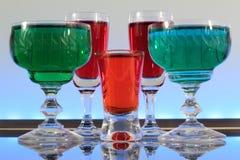Close-up van een lijn van kleurrijke cocktails die op de bar met geleide verlichting rusten bij een club Stock Foto