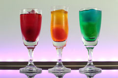 Close-up van een lijn van kleurrijke cocktails die op de bar met geleide verlichting rusten bij een club Stock Fotografie