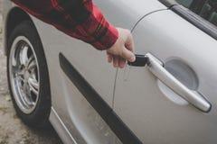 Close-up van een man hand die een sleutel opneemt in het deurslot van een auto De onherkenbare witte mens opent voertuigdeur door stock foto