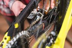 Close-up van een man hand, door meesters wordt het geleid, smeert de fietsketting van een bergfiets met een speciaal smeermiddel  royalty-vrije stock foto