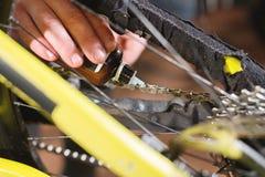 Close-up van een man hand, door meesters wordt het geleid, smeert de fietsketting van een bergfiets met een speciaal smeermiddel  royalty-vrije stock fotografie