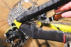 Close-up van een man hand, door meesters wordt het geleid, smeert de fietsketting van een bergfiets met een speciaal smeermiddel  stock afbeeldingen