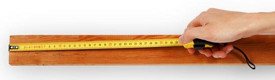 Close-up van een mannelijke hand die metend band op houten raad gebruiken royalty-vrije stock fotografie