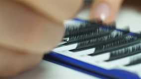 Close-up van een meester bij close-up van het de uitbreidingenmateriaal van de het werk het kunstmatige wimper van een meester op stock footage