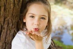 Close-up van een meisje die een kus blazen bij park stock afbeelding