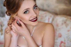 Close-up van een meisje die en op oorringen in haar oren glimlachen zetten Het model met rode lippen en met grote grijze ogen gli stock foto