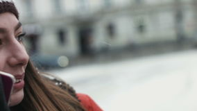Close-up van een meisje die op cellphone in openlucht op de winterdag spreken De jonge vrouw heeft een zoet gesprek op telefoon t stock video