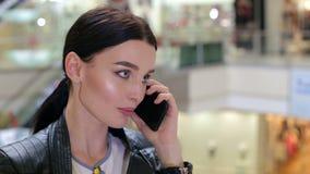 Close-up van een meisje in een leerjasje die op de telefoon in een winkelcentrum spreken stock videobeelden