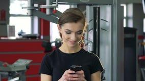 Close-up van een meisje met een telefoon in de gymnastiek stock videobeelden