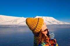 Close-up van een meisje in een regenboogjasje en geel gebreid GLB op de achtergrond Svalbard Longyearbyen van het bergnoorden p stock afbeelding