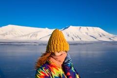 Close-up van een meisje in een regenboogjasje en geel gebreid GLB op de achtergrond Svalbard Longyearbyen van het bergnoorden p stock fotografie